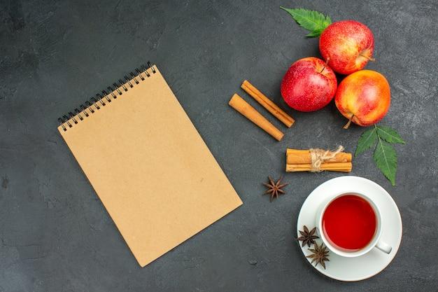 Horizontale weergave van verse natuurlijke biologische rode appels met groene bladeren, kaneellimoenen en notitieboekje een kopje thee op zwarte achtergrond