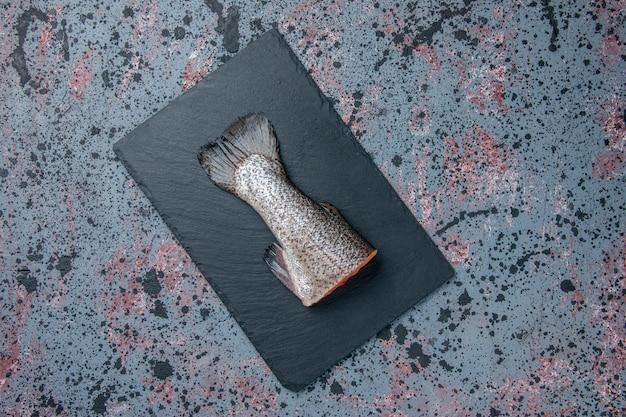 Horizontale weergave van verse rauwe vis op donkere kleur lade op blauw zwart mix kleuren tafel met vrije ruimte