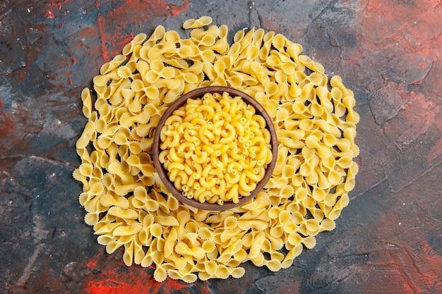 Horizontale weergave van vlinder ongekookte pasta's in een bruine kom op gemengde kleurentafel