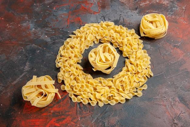 Horizontale weergave van vlinder pasta en spaggeti op gemengde kleur tabel stock foto