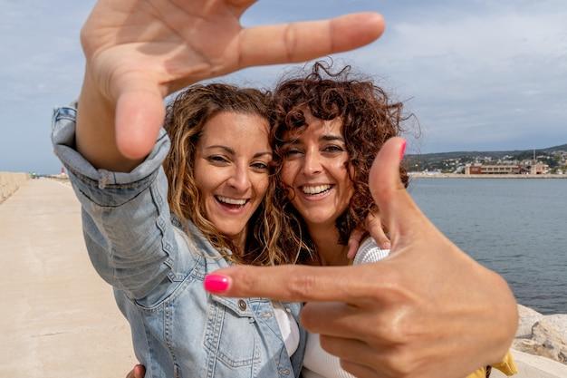 Horizontale weergave van vriendinnen die plezier hebben met het inlijsten van gezichten. vriendschap en vakantie reizen concept.