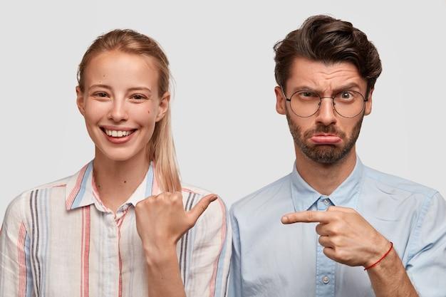 Horizontale weergave van vrolijke europese jonge vrouw met paardenstaart, gekleed in overhemd, wijst naar haar ontevreden echtgenoot die een mislukking heeft, model tegen witte muur. relatie concept