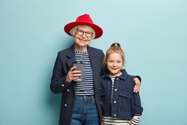 Horizontale weergave van vrolijke grootmoeder draagt stijlvolle rode hoed, zwarte jas