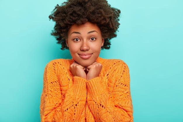 Horizontale weergave van vrolijke nieuwsgierige verrast afro-amerikaanse dame met donker borstelig haar, kin raakt met beide handen, gekleed in levendige oranje trui, geïsoleerd op blauwe muur