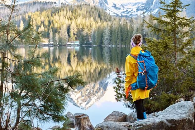 Horizontale weergave van vrouwelijke toerist geniet van rustige afgelegen bergzicht op het meer, staat terug naar de camera