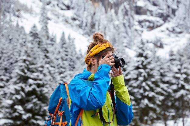 Horizontale weergave van vrouwelijke wandelaar poses in besneeuwde bergen, top bereikt, maakt foto met camera vanaf heuvel
