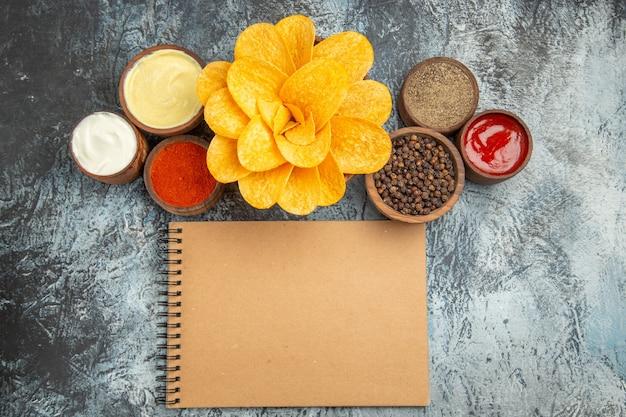 Horizontale weergave van zelfgemaakte aardappelchips ingericht als vormige bloem en notebook op grijze tafel