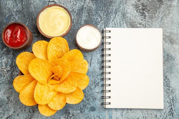 Horizontale weergave van zelfgemaakte aardappelchips versierd als gevormde bloem en zout met ketchup mayonaise en notebook op grijze tafel