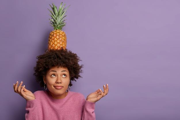 Horizontale weergave van zwarte krullende vrouw probeert evenwicht te bewaren, houdt verse ananas op het hoofd, spreidt handpalmen, kijkt naar boven