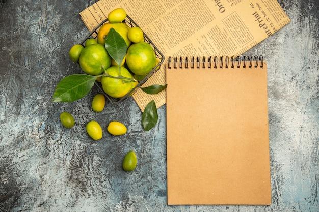 Horizontale weergave van zwarte mand met verse groene mandarijnen en kumquats op kranten en notitieboekje op grijze achtergrond