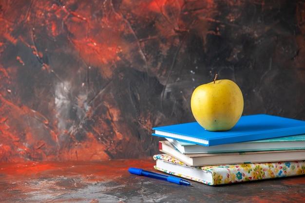 Horizontale weergave verse gele appel op gestapelde notebooks aan de linkerkant op donkere achtergrond