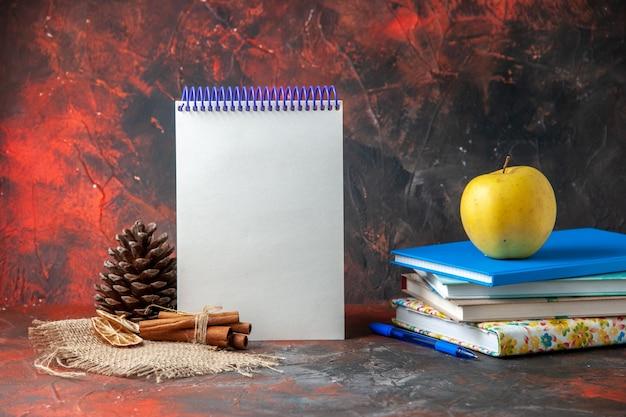 Horizontale weergave verse gele appel op gestapelde notebooks coniferenkegel en kaneellimoenen op donkere achtergrond