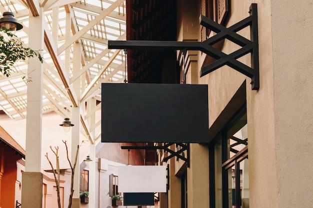 Horizontale zwarte lege signage op de voorkant van de kledingwinkel met exemplaarruimte.
