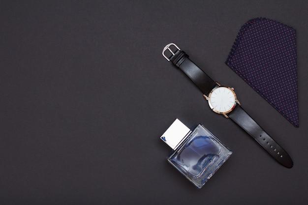 Horloge met een zwarte leren band, cologne voor mannen en zakdoek op grijze achtergrond. accessoires voor heren. bovenaanzicht met kopie ruimte.