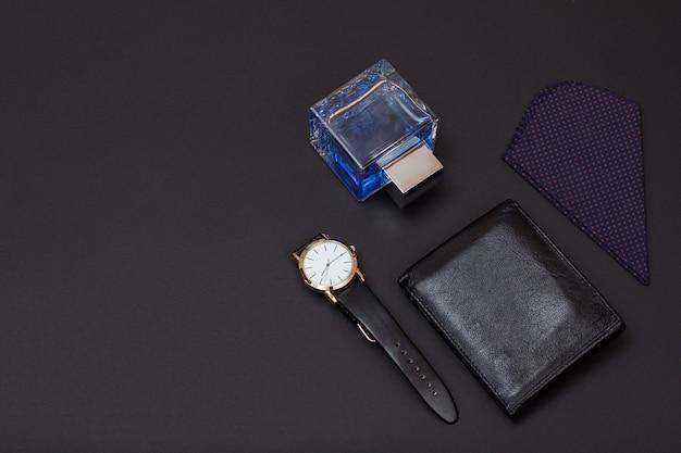 Horloge met een zwarte leren band, leren portemonnee, cologne voor mannen en zakdoek op zwarte achtergrond. accessoires voor heren. bovenaanzicht met kopie ruimte.