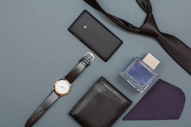 Horloge met een zwarte leren band, mobiele telefoon, leren portemonnee, cologne voor mannen, zakdoek en stropdas op grijze achtergrond. accessoires voor heren. bovenaanzicht met kopieerruimte