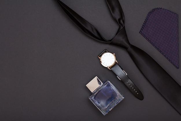 Horloge met zwarte leren band, cologne voor heren, zakdoek en stropdas op zwarte achtergrond. accessoires voor heren. bovenaanzicht met kopie ruimte.
