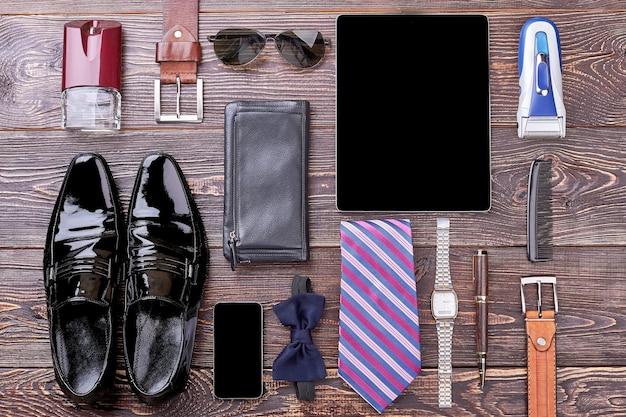 Horloge, schoenen en gadgets. vlinderdas, portemonnee en eau de cologne. goed kijken door een paar stappen.