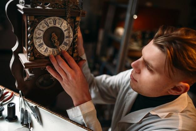 Horlogemaker past het mechanisme van oude horloges aan