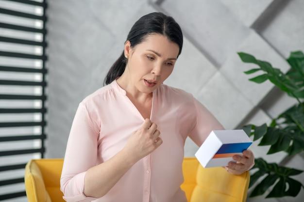 Hormoonvervangende therapie. volwassen mooie vrouw die met harmonischenpillen in haar handen interessant kijkt