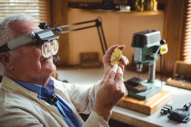 Horoloog die een klokdeel onderzoekt