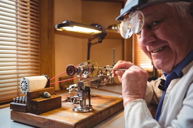 Horoloog repareren van een horloge in de werkplaats