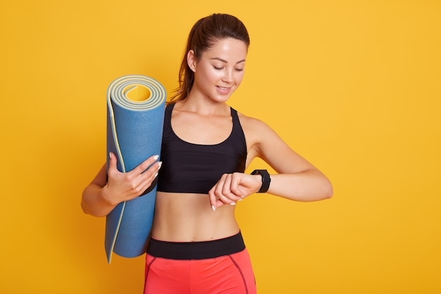 Horozontal schot van fitness vrouw na training sessie controleert resultaten op smartwatch in fitness app, vrouw met pefect lichaam geïsoleerd op gele achtergrond. gezonde levensstijl en sport concept.
