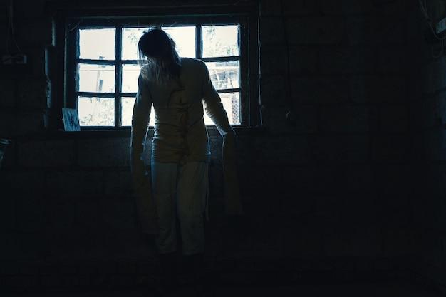 Horror voor halloween-vakantie crazy man in een vies meetshirt in een oud verwoest huis is op slot en maakt iedereen bang om een slachtoffer te verwachten