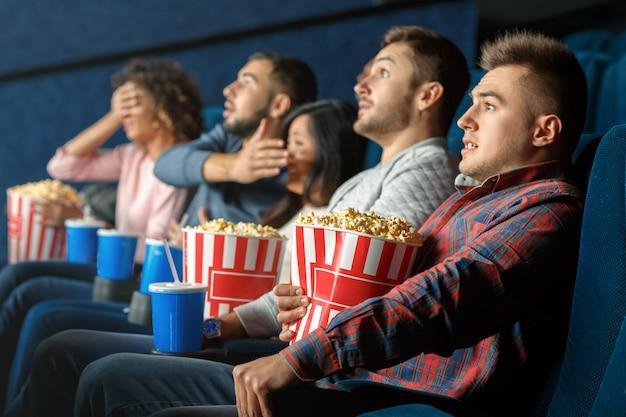 Horrorfilms marathon. jonge man op zoek bang zitten in de bioscoop met zijn vrienden