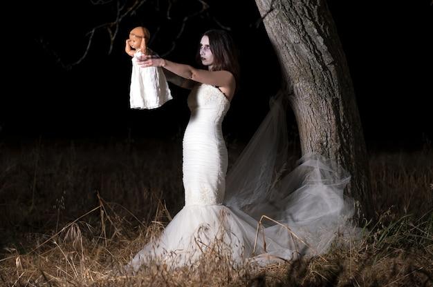 Horrorscène van een bezeten vrouw die een pop vasthoudt