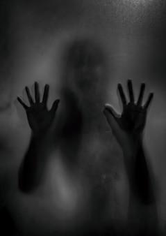 Horrorspook meisje achter het matte glas in zwart en wit. halloween-festivalconcept.
