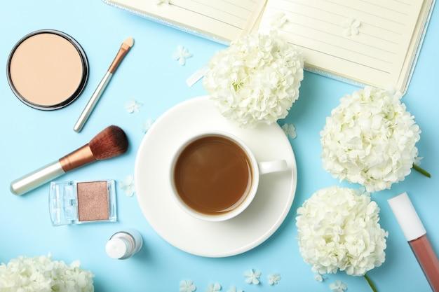 Hortensia bloemen, koffie en cosmetica op blauwe achtergrond