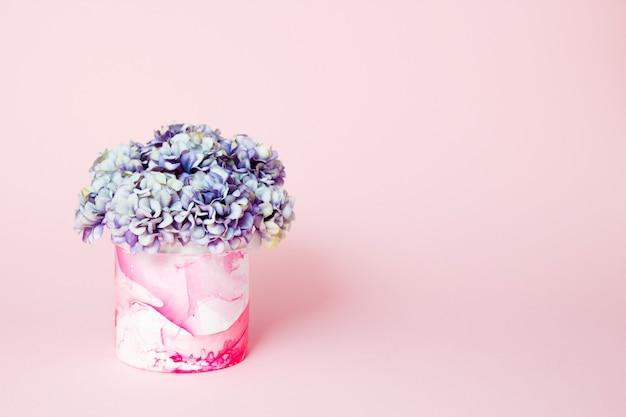 Hortensia's in een decoratieve abstracte vaas op roze