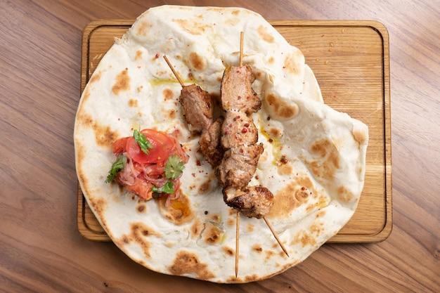 Hot beef kebab met tomaten, uien en vers gebakken tortilla op een houten snijplank.