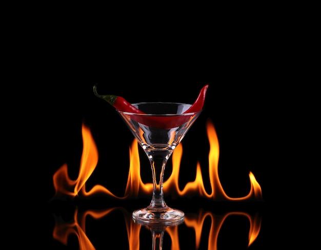 Hot chili peper in een martiniglas met een vuur op een zwarte achtergrond