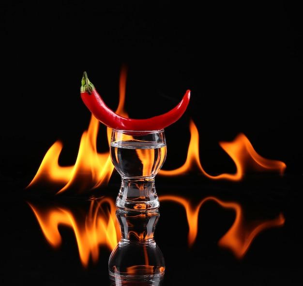 Hot chili peper in een shot glas met een vuur op een zwarte achtergrond