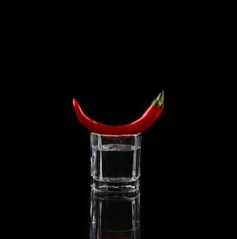 Hot chili peper in een shot glas met een vuur op zwart