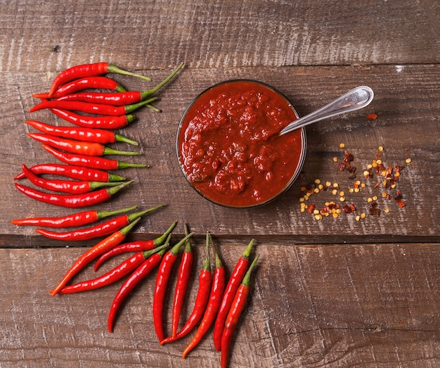 Hot chili pepersaus pasta harissa, traditionele tunesië, marokkaanse, arabische keuken adjika, chili peper kruiden en verse rode chilipepers, over houten tafel.