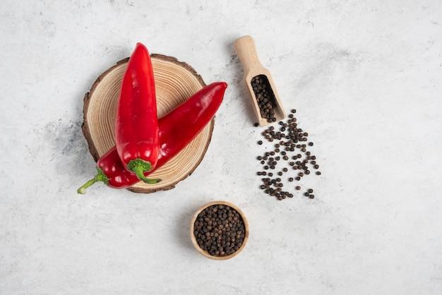 Hot chili peppers en peperkorrels op marmeren achtergrond.