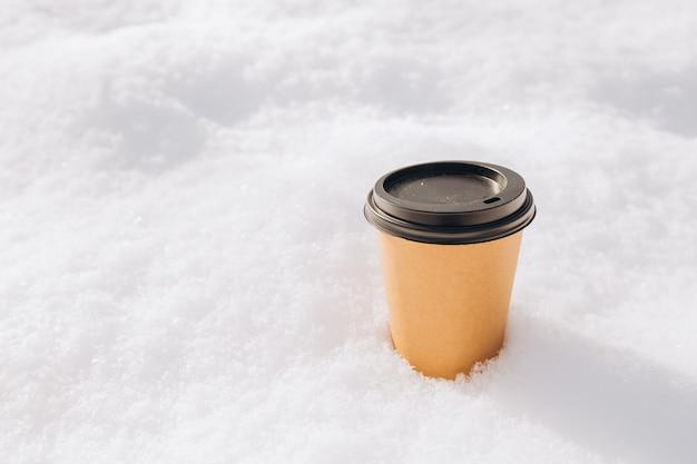 Hot paper craft kopje koffie op de sneeuw op een ochtend. afhaal- of leveringsconcept. ruimte kopiëren. winterse levensstijl. plaats voor uw tekst of logo op mok, mockup