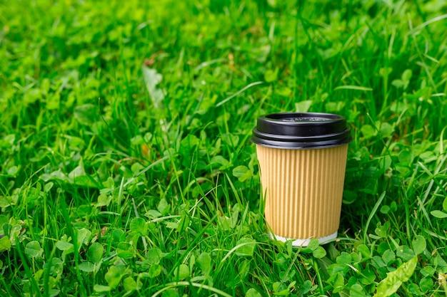 Hot paper craft kopje koffie op het gras op een ochtend. afhaal- of leveringsconcept. ruimte kopiëren. zomer levensstijl. plaats voor uw tekst of logo op mok, mockup