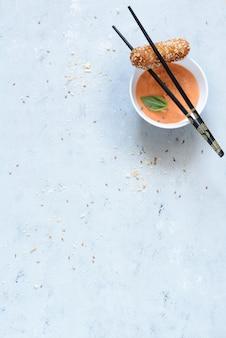 Hot roll van kaas en kip in paneermeel van paneermeel en sesam met verse groenten en sauzen. heerlijk eten in aziatische stijl kopieer de ruimte