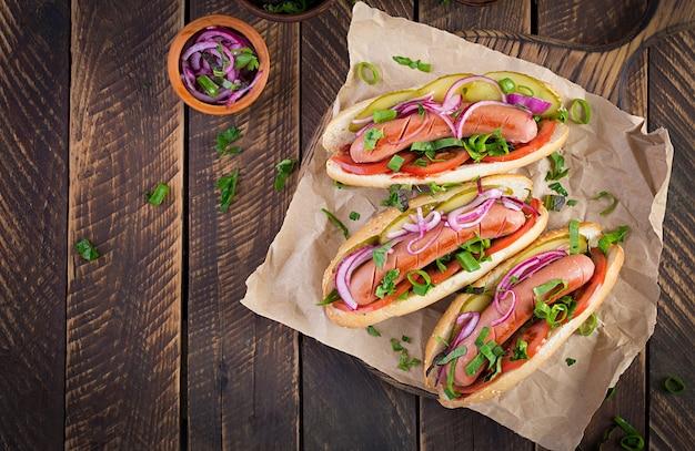 Hotdog met augurken, tomaat en sla op houten achtergrond. hotdog, amerikaanse keuken. bovenaanzicht, hierboven, kopieer ruimte