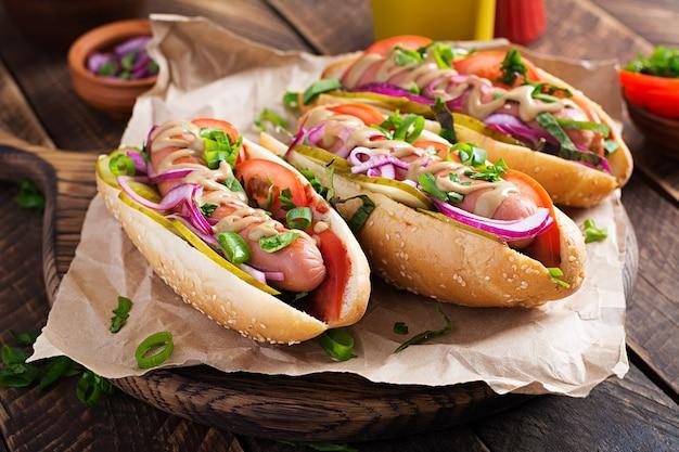 Hotdog met augurken, tomaat en sla op houten achtergrond. hotdog, amerikaanse keuken.