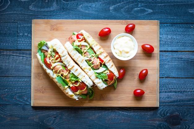 Hotdog met augurken, tomaten en olijven
