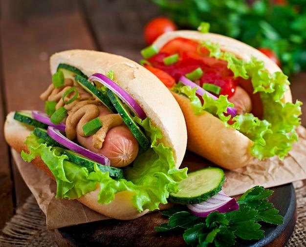 Hotdog met ketchup, mosterd, sla en groenten op houten tafel