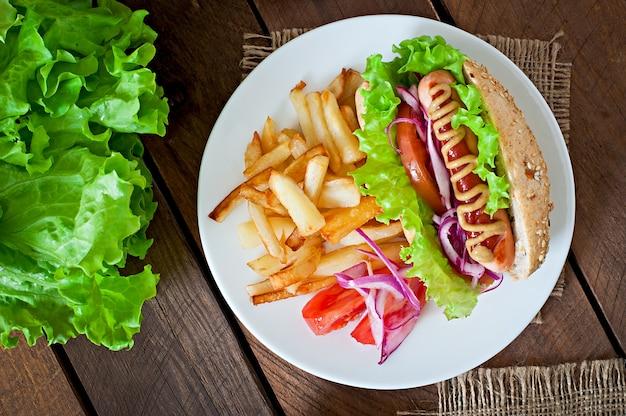 Hotdog met ketchupmosterd en sla op houten lijst.