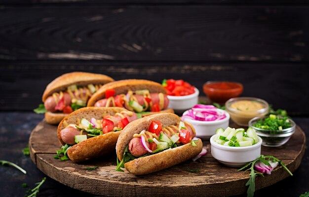 Hotdog met komkommer, tomaat en rode ui op houten oppervlak.