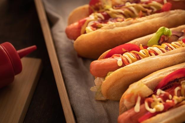 Hotdog met peper, tomaat, sla en salade mix op houten.