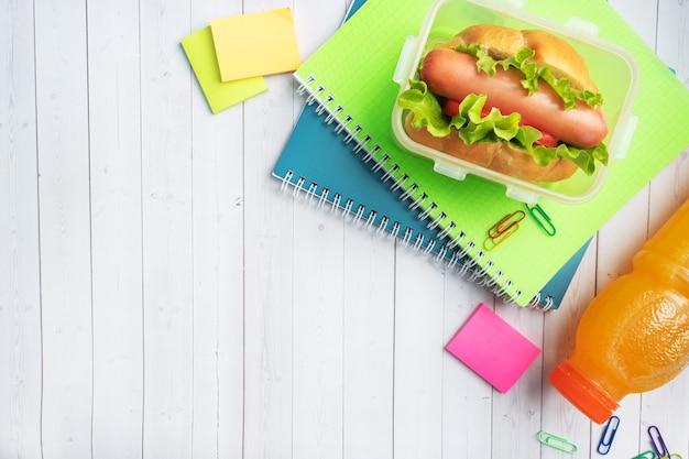 Hotdog met slatomaat en worst. notitieboekjes en briefpapier. concept school ontbijt. kopieer ruimte.